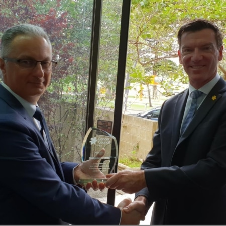 Photo of David Baruffi, Practice Principal and Ashley Reid, CEO of Cancer Council WA, shaking hands and holding commemorative plaque.