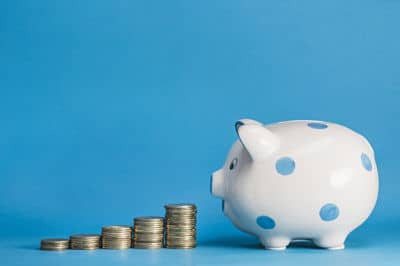 White and blue polka dot piggy bank looking at a stack of coins.