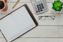 Image of calculator, glasses and notepad.