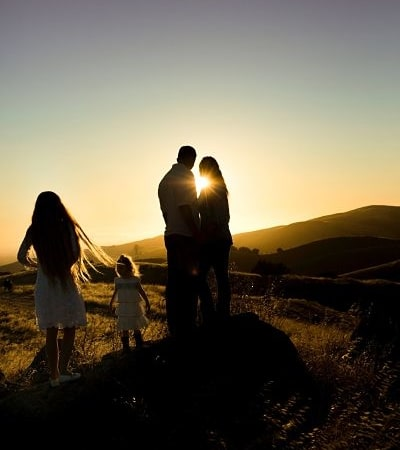 Family watching sunset on hill.