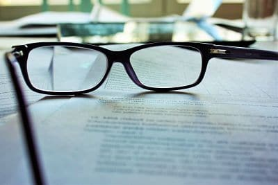 Black rim glasses resting on a book.