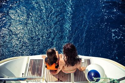 Girl and her mother enjoying vacation on sailboat