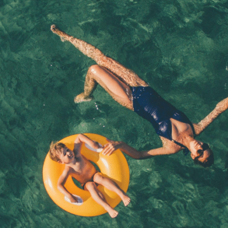 Woman floating in the ocean on her back side by side with young girl on yellow doughnut inflatable.